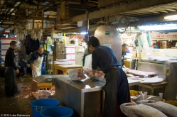 Worker sawing frozen tuna, Tsukiji Fish Market