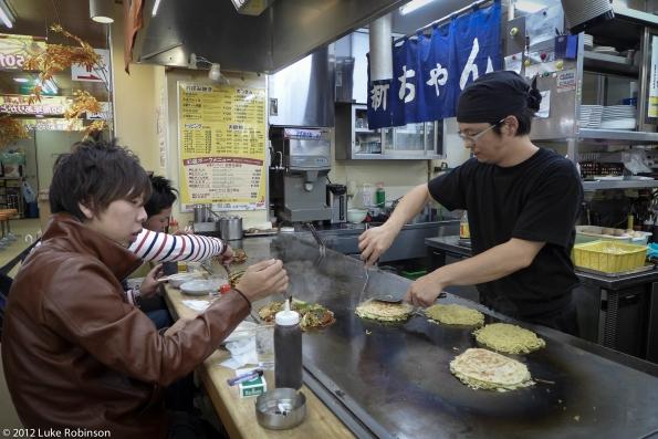 Serving Hiroshima-style Okonomiyaki, Okonomi-mura, Hiroshima