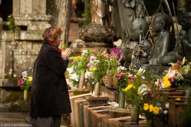 Woman making offering to Jizō Statues, Oku-no-in Cemetery, Koya